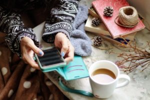 Person on mobile phone with cup of tea